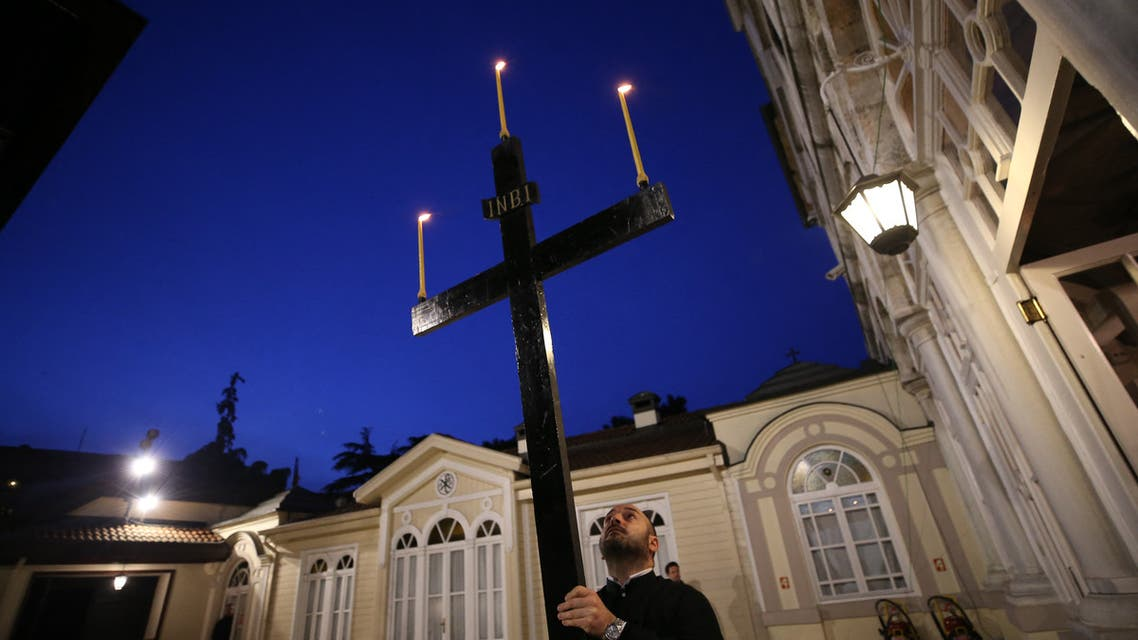 A priest holds a cross during the Good Friday procession of the Epitaphion/Shroud led by Ecumenical Patriarch Bartholomew I, the spiritual leader of the world's Orthodox Christians, during Orthodox Easter Week services, held without worshippers to help contain the spread of the coronavirus at the Patriarchal Church of St. George in Istanbul on April 17, 2020. (File photo: AFP)