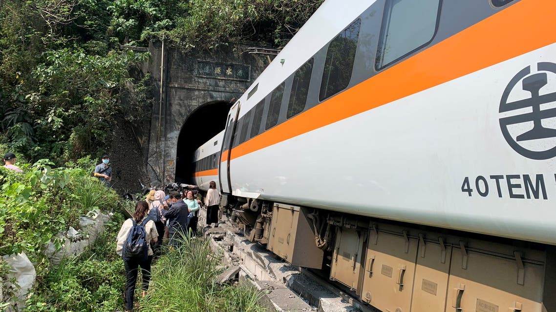 People walk next to a train which derailed in a tunnel north of Hualien, Taiwan. (Reuters)