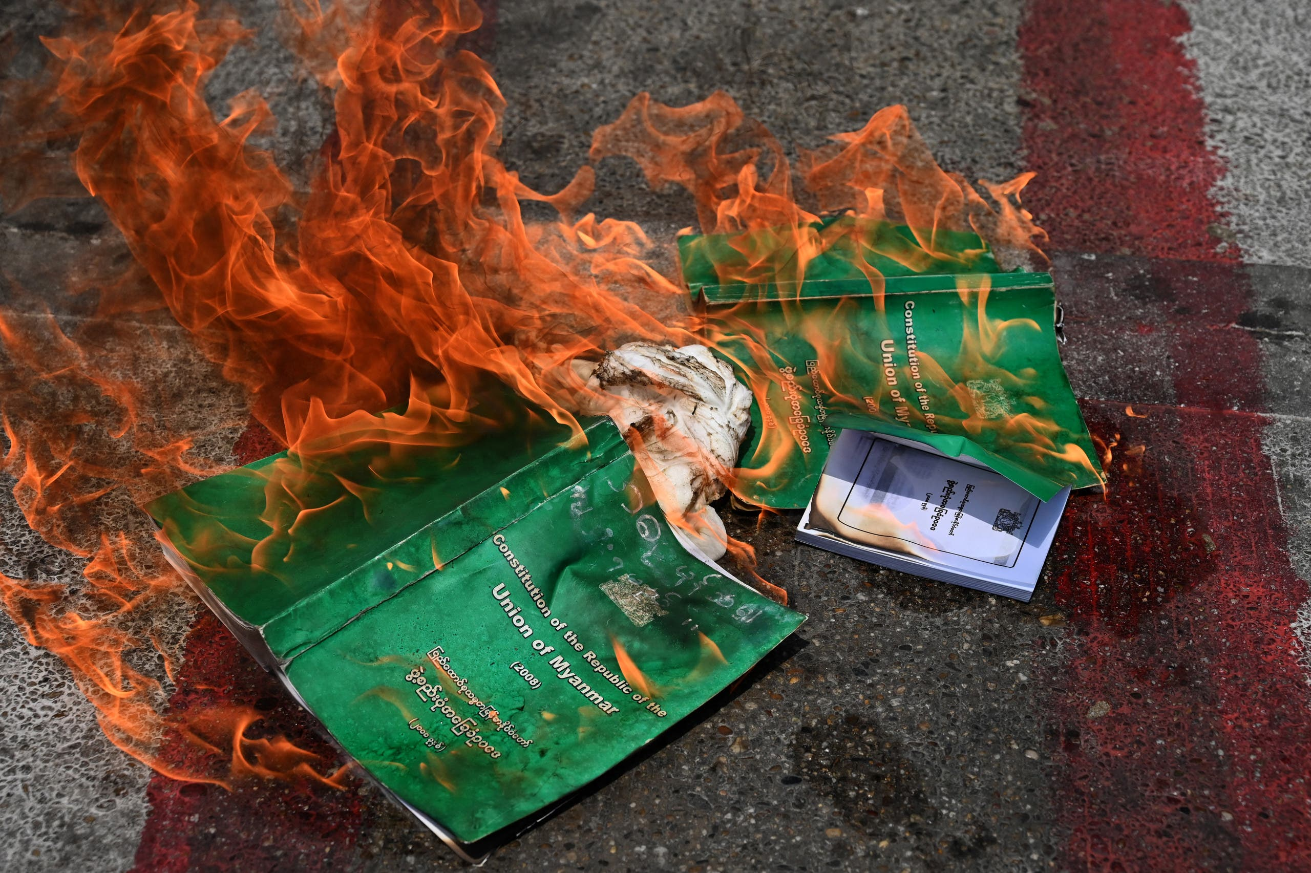 Copies of the 2008 constitution are burnt during a demonstration by protesters against the military coup in Yangon's South Okkalapa township on April 1, 2021. (File photo: AFP)