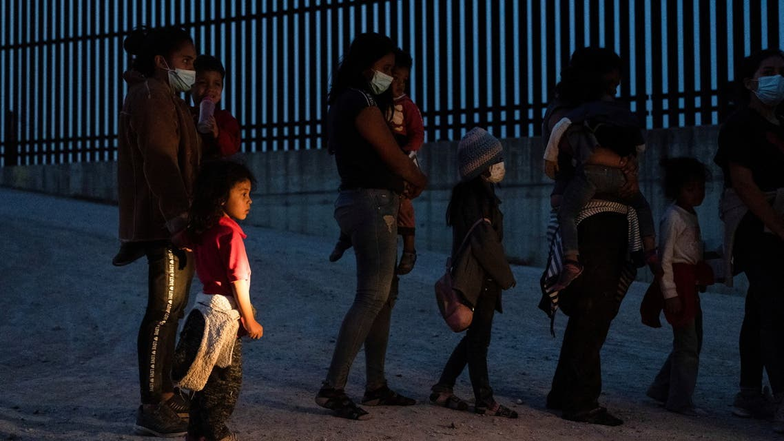 Asylum-seeking migrants' families make a line to board a bus as they wait to be transported by the U.S. Border Patrols after crossing the Rio Grande river into the United States from Mexico in Penitas, Texas, U.S., March 26, 2021. (Reuters)