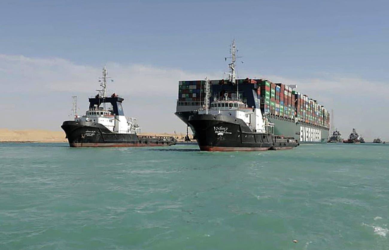 عکس منتشر شده توسط مقامات کانال سوئز در تاریخ 29 مارس 2021 ، نشان دهنده قایق در حال یدک کشیدن کشتی کانتینر MV Evergiven