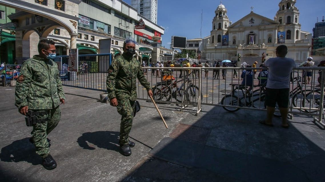 Police officers patrol as Roman Catholic devotees gather in front of Quiapo church during Good Friday in Manila on April 2, 2021, after the government imposed strict lockdowns to cope with a surge in COVID-19 infections. (Jam Sta Rosa/AFP)
