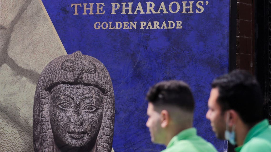 Men pass in front of poster for pharaohs golden parade after the renovation of Tahrir Square for transferring 22 mummies. (Reuters)