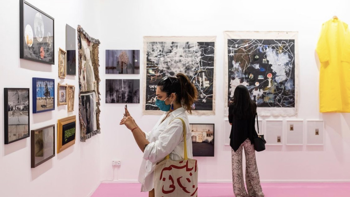 Art Dubai attendee takes a photo of a display at the Athr Gallery booth showcasing work by Saudi artists. (Instagram)