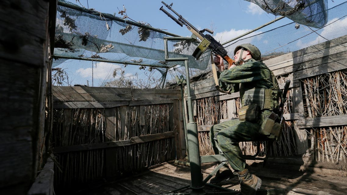 A militant of the self-proclaimed Donetsk People's Republic (DNR) points a weapon at fighting positions on the line of separation from the Ukrainian armed forces south of the rebel-controlled city of Donetsk, Ukraine April 2, 2021. REUTERS/Alexander Ermochenko