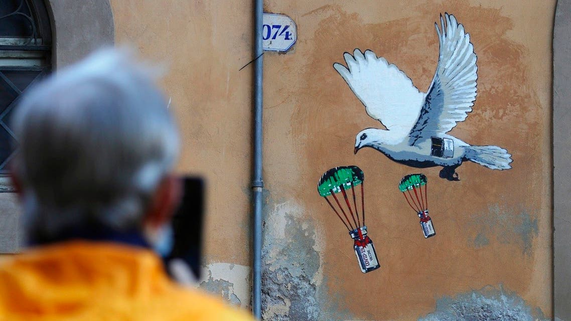 A man takes a picture of a mural depicting a white dove parachuting COVID-19 vaccine vials, posted near the Italian Health Ministry Headquarters in Rome, Sunday, April 4, 2021. (AP/Gregorio Borgia)