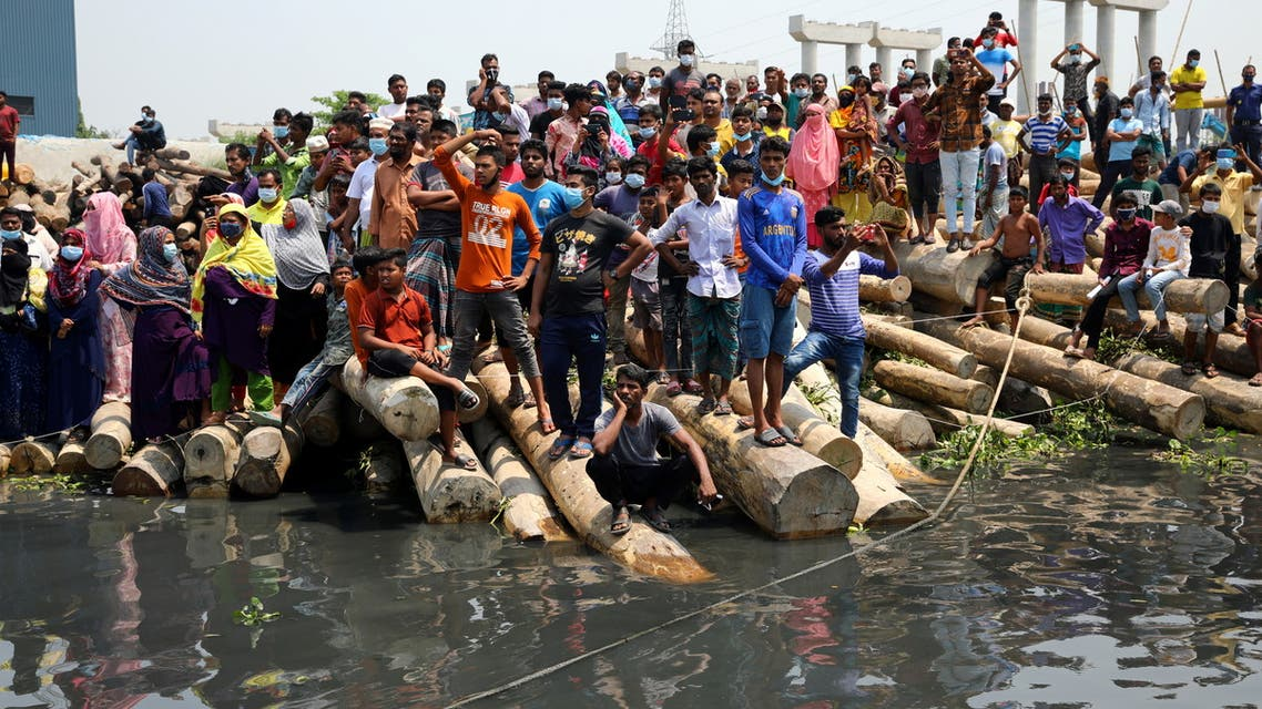 Relatives and onlookers watch the rescue operation of a ferry that collided with a cargo vessel and sank on Sunday in the Shitalakhsyaa River, in Narayanganj, Bangladesh, April 5, 2021. (Reuters)