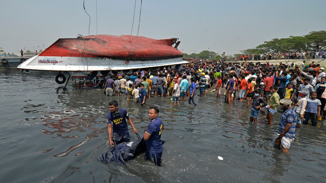 Divers carry a body after recovering from the capsized boat in Shitalakshya River, in Narayanganj on April 5, 2021. (AFP)