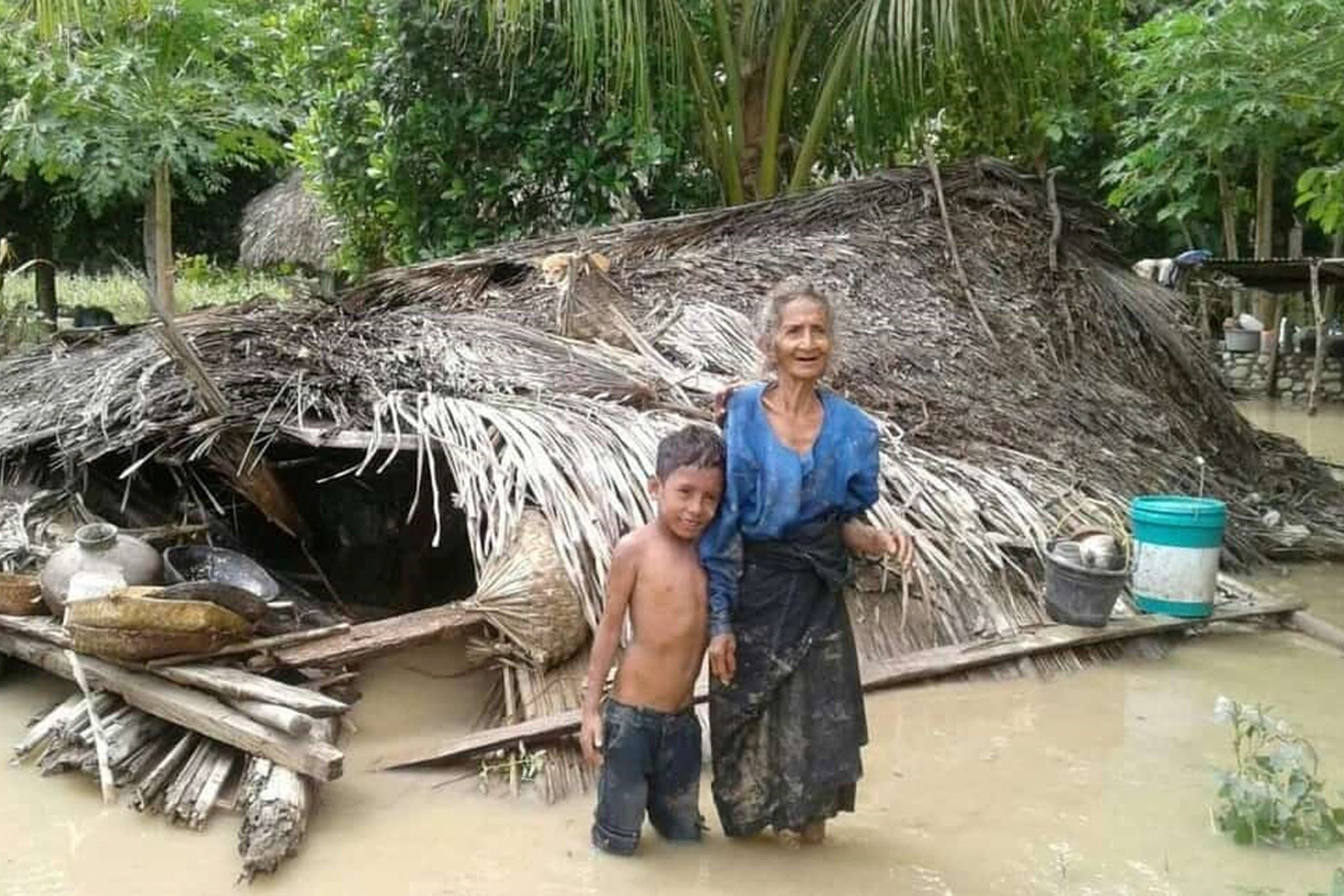 An elderly villager and her grandson stand in floodwaters in front of their damaged home in the village of Haitimuk in East Flores on April 4, 2021, after flash floods and landslides swept eastern Indonesia and neighbouring East Timor. (File photo: AFP)