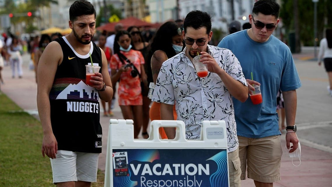 A group of men read public safety precautions while enjoying the bars and restaurants on South Beach during Spring Break amid the COVID-19 pandemic, March 27, 2021. (Reuters)