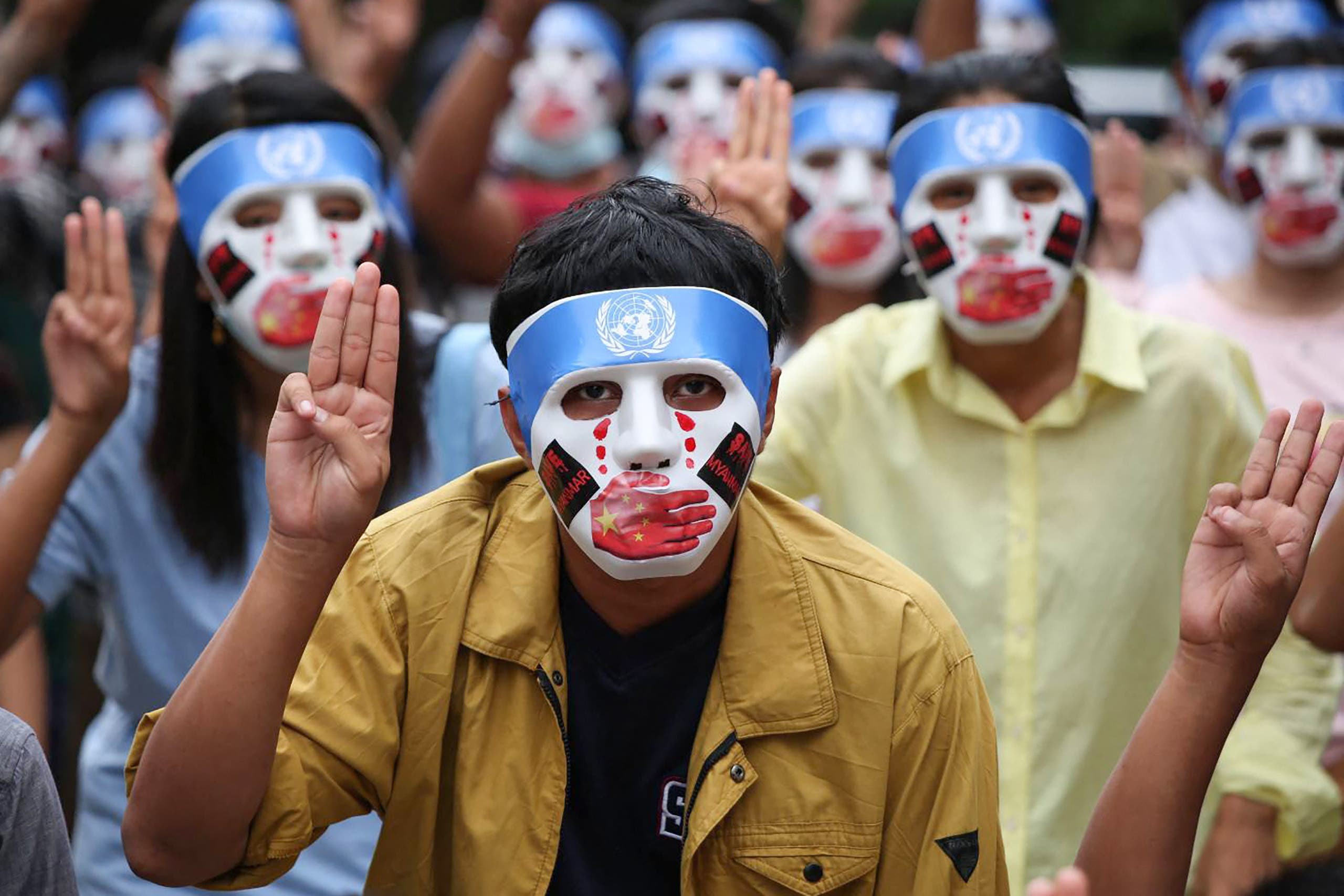 This handout from the Burma Associated Press (BAP) taken and received on April 4, 2021 shows protesters making the three-finger salute while wearing masks that express what they say is Chinese interference in the UN's handling of Myanmar affairs after the military coup in Yangon's Kamayut township. (File photo: AFP)