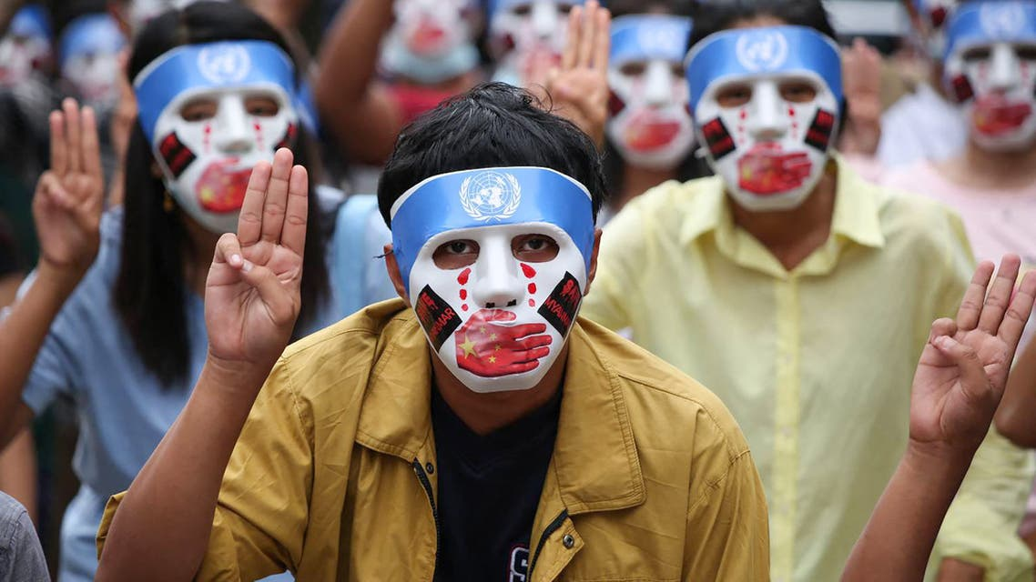 his handout from the Burma Associated Press (BAP) taken and received on April 4, 2021 shows protesters making the three-finger salute while wearing masks that express what they say is Chinese interference in the UN's handling of Myanmar affairs after the military coup in Yangon's Kamayut township. (File photo: AFP)