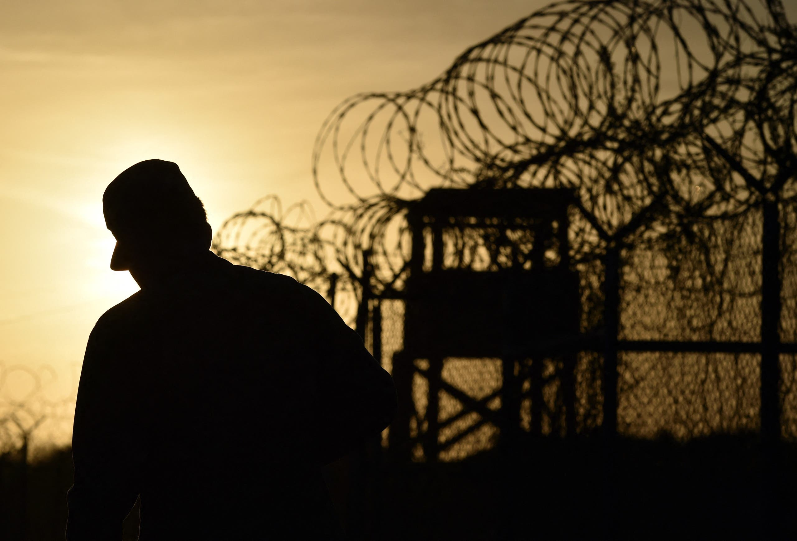 This photo made during an escorted visit and reviewed by the US military, shows an US soldier walking next to the razor wire-topped fence at the abandoned Camp X-Ray detention facility at the US Naval Station in Guantanamo Bay, Cuba, April 9, 2014. (AFP)