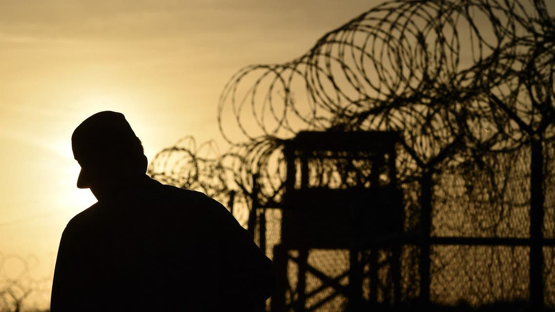 This photo made during an escorted visit and reviewed by the US military, shows an US soldier walking next to the razor wire-topped fence at the abandoned Camp X-Ray detention facility at the US Naval Station in Guantanamo Bay, Cuba, April 9, 2014. AFP PHOTO/MLADEN ANTONOV