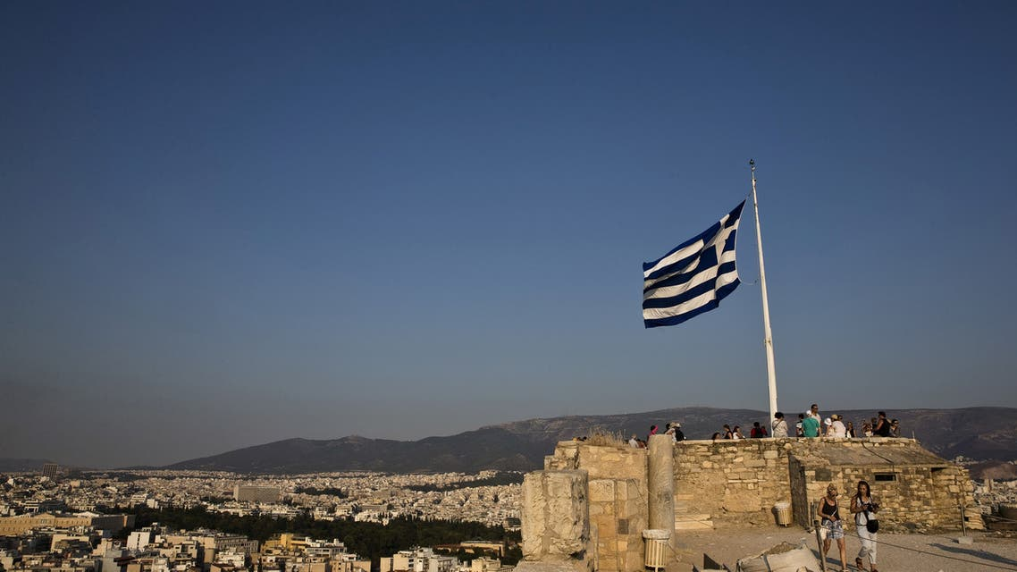 A Greek flag flutters in the wind as tourists visit the archaeological site of the Acropolis hill in Athens, Greece. (File photo: Reuters)
