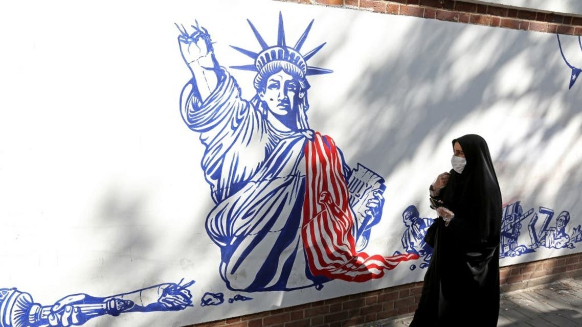 A woman, wearing a protective mask amid the COVID-19 pandemic, walks past a mural painted on the outer walls of the former US embassy in the Iranian capital Tehran on September 20, 2020. (AFP)
