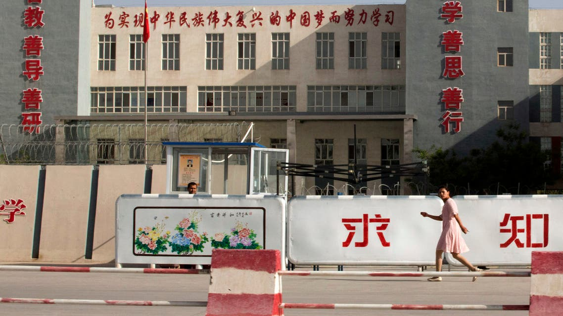 In this Aug. 31, 2018, file photo, a woman walks past the Kashgar Dongcheng No. 4 Junior Middle School, which is part of a cluster of schools with slogans which read, Study hard to realize the Chinese dream of the great rejuvenation of the Chinese nation, Kind Learning, Kind Thoughts, Kind Actions, and Pursue Knowledge, on the outskirts of in Kashgar, western China's Xinjiang region. (File photo: AP)