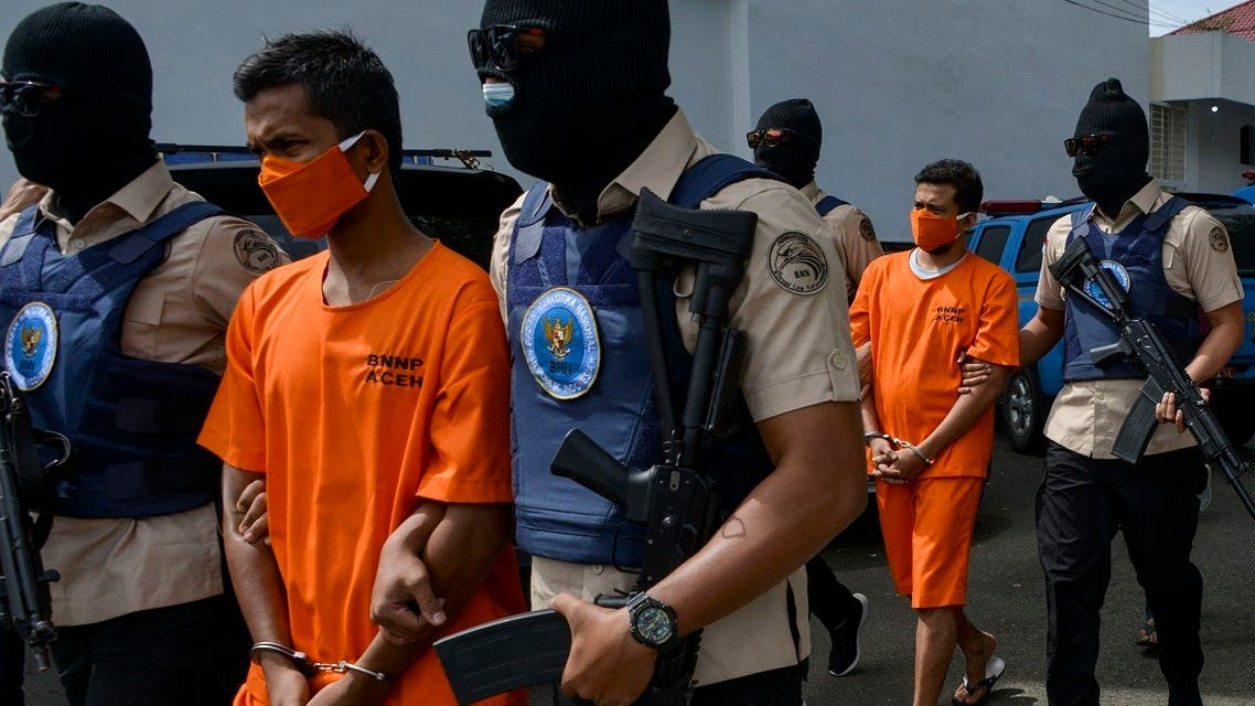 Indonesian National Narcotic Agency (BNN) officers escort two local men suspected of smuggling methamphetamine at a press conference in Banda Aceh on October 13, 2020. (AFP)