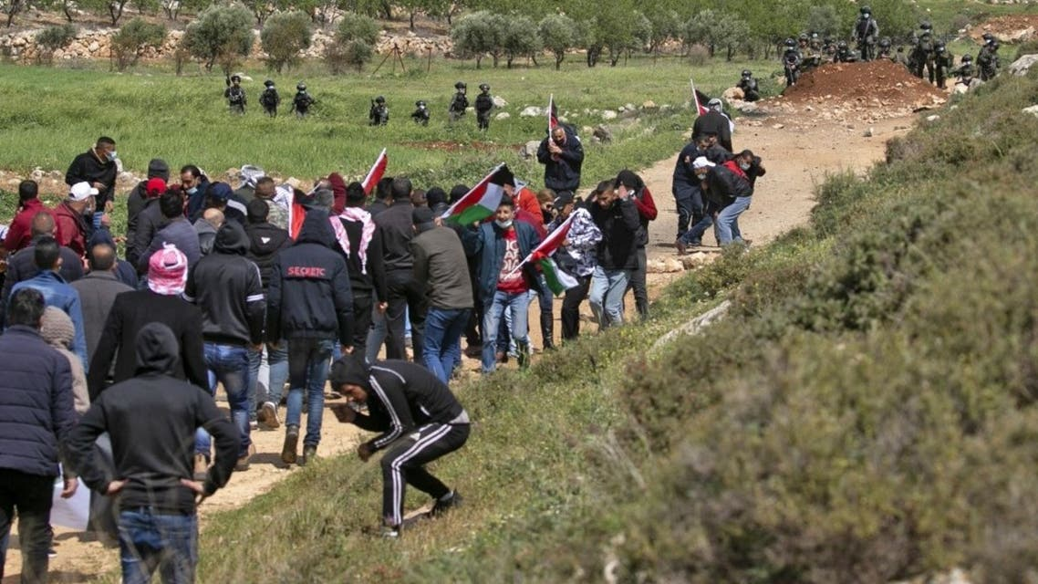Israeli security forces keep watch as Palestinians protest against the establishment of Israeli outposts in their lands, on March 26, 2021 in Beit Dajan, east of Nablus in the occupied West Bank. (AFP)