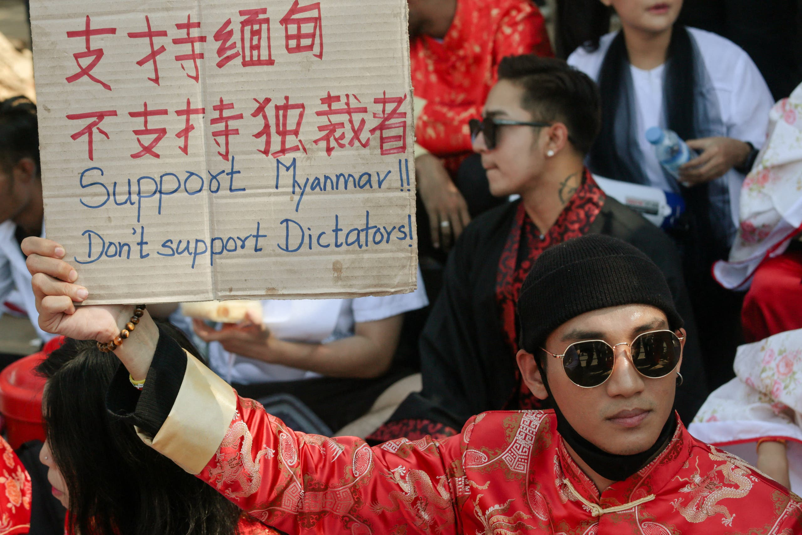In this file photo taken on February 11, 2021, model, actor and singer Paing Takhon wears a traditional Chinese outfit while holding a sign during a demonstration against the military coup in front of the Chinese embassy in Yangon. (File photo: AFP)