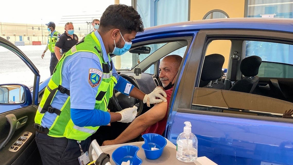 A health worker inoculates a man against the coronavirus at a drive-through vaccination center in the city of al-Wakrah, north of the capital Doha, on March 31, 2021. (Anne Levasseur/AFP)