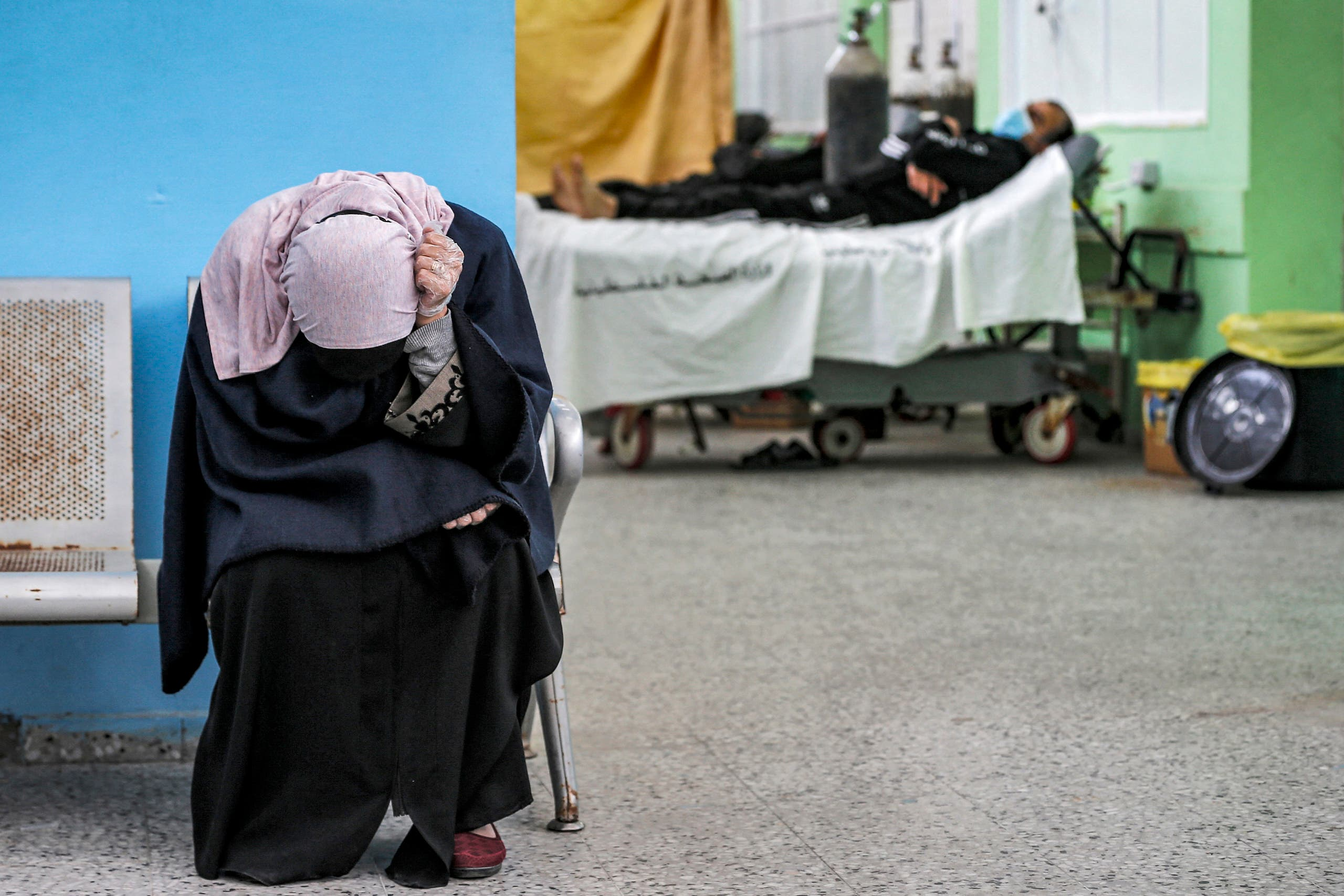 A Palestinian woman reacts while waiting for her husband (background) at the COVID-19 intensive care unit of al-Shifa Hospital in Gaza City on April 7, 2021. (File photo: AFP)