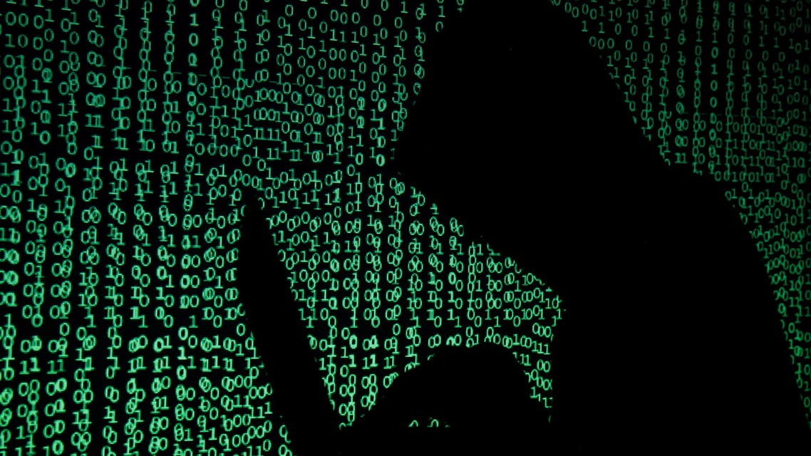 A hooded man holds a laptop computer as cyber code is projected on him in this illustration picture taken on May 13, 2017. (Reuters)