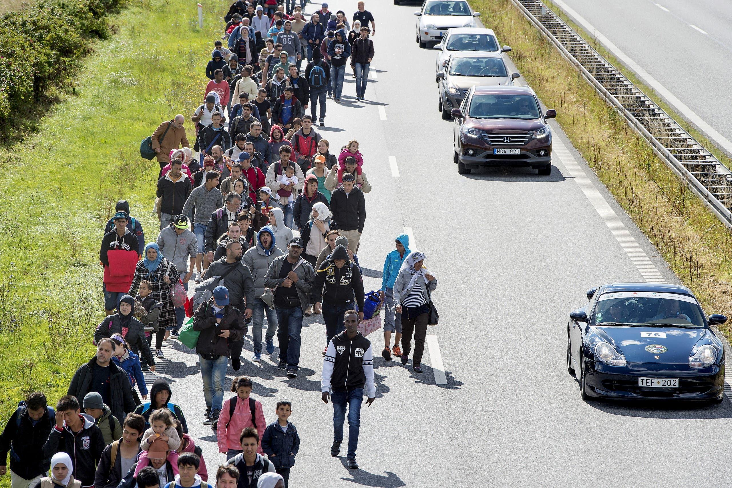 مهاجرون يعبرون الدنمارك للووصل إلى السويد خلال موجة الهجرة الجماعية في أوروبا في 2015