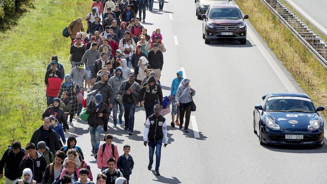 مهاجرون يعبرون الدنمارك للصوصل إلى السويد خلال موجة الهجرة الجنماعيتة في أوروبا في 2015