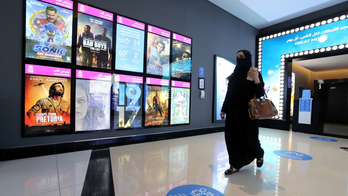 A Saudi woman wearing a protective mask walks past the movie screen board at VOX Cinema in Riyadh Park Mall, after the government lifted the coronavirus lockdown restrictions in Riyadh, Saudi Arabia June 25, 2020. REUTERS/Ahmed Yosri