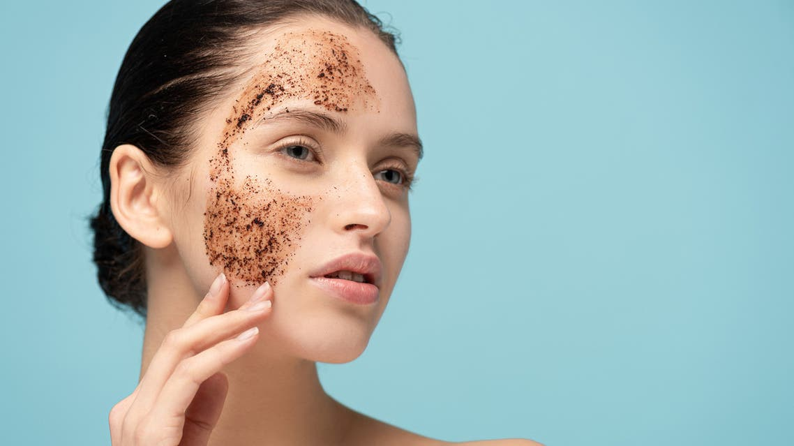 Beautiful woman applying coffee scrub on face, isolated on blue stock photo