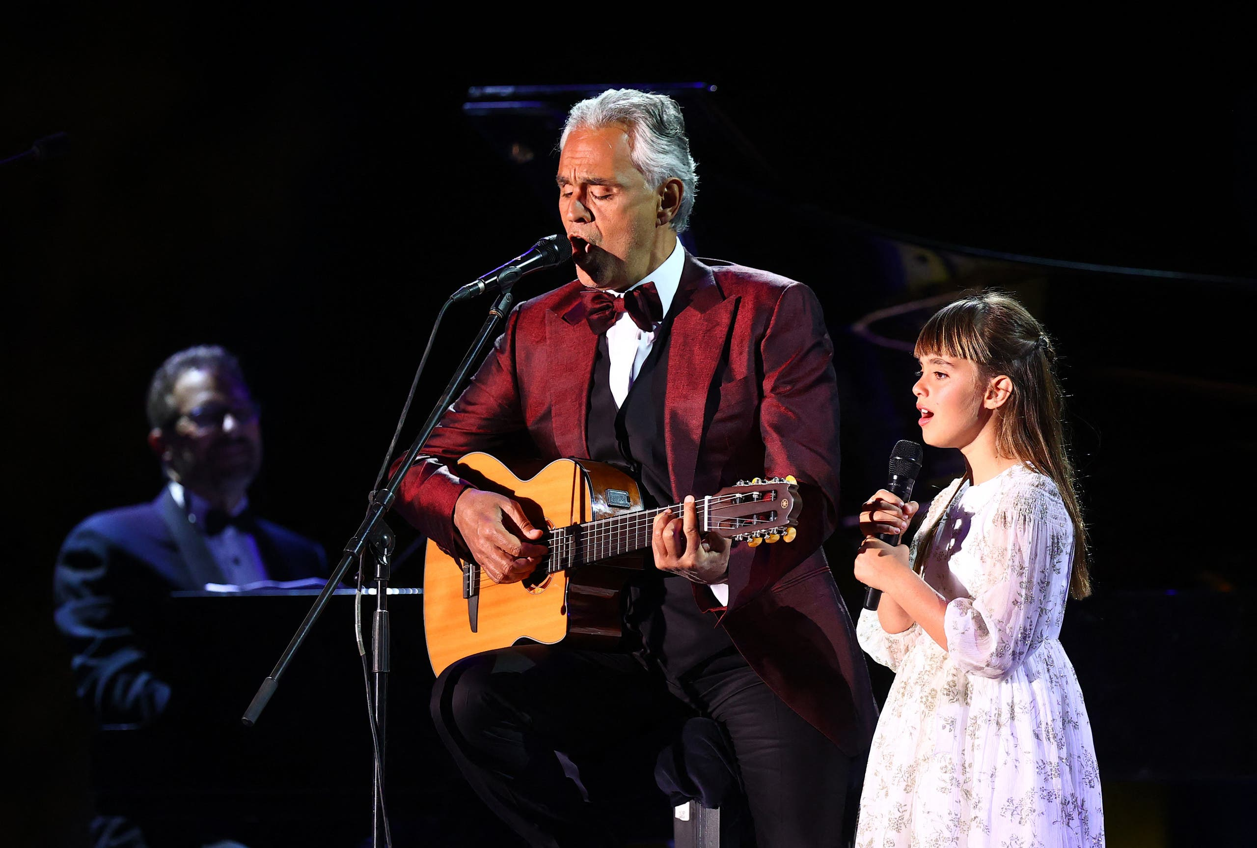 Italian tenor and opera singer Andrea Bocelli and his daughter Virginia singing during a concert at the Hegra World Heritage Site in the northwestern Saudi city of al-Ula on April 8, 2021. (AFP)