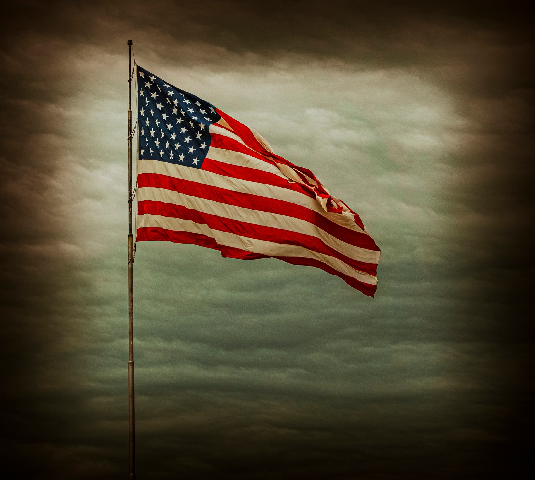 Flag of the United States of America against the background of black clouds before a hurricane. (Stock photo)