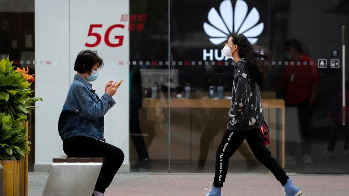 A woman wearing a face mask to help curb the spread of the coronavirus browses her smartphone as a masked woman walks by the Huawei retail shop promoting it 5G network in Beijing. (File photo: AP)