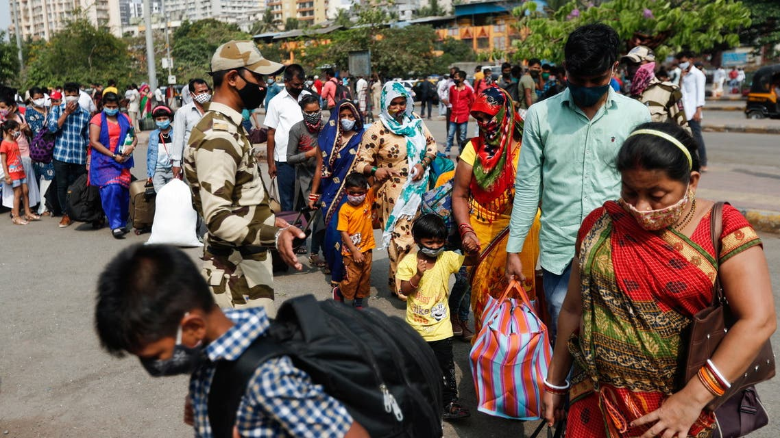 People wearing protective masks walk in a line at a railway station amidst the spread of the coronavirus disease (COVID-19) in Mumbai, India, 9 April, 2021. (Reuters)