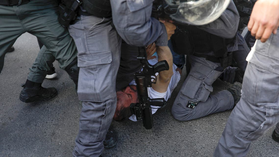 Israeli policemen detain Israeli MP Ofer Cassif, a Jewish member of the predominantly Arab Joint List electoral alliance. (AFP)