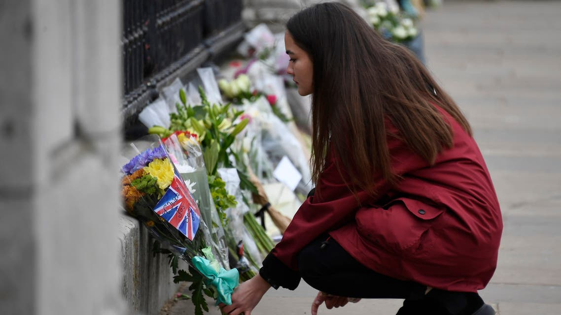 A woman places flowers at the gate of Buckingham Palace in London, one day after the death of Britain's Prince Philip, Saturday, April 10, 2021. Britain's Prince Philip, the irascible and tough-minded husband of Queen Elizabeth II who spent more than seven decades supporting his wife in a role that mostly defined his life, died on Friday. (AP Photo/Alberto Pezzali)