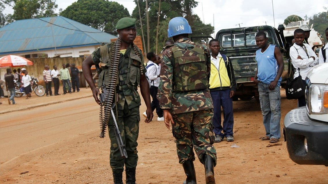 A peacekeeper serving in the MONUSCO and a Congolese soldier stand guard as residents gather following recent demonstrations in Beni in North Kivu province, October 23, 2014. (Reuters/Kenny Katombe)