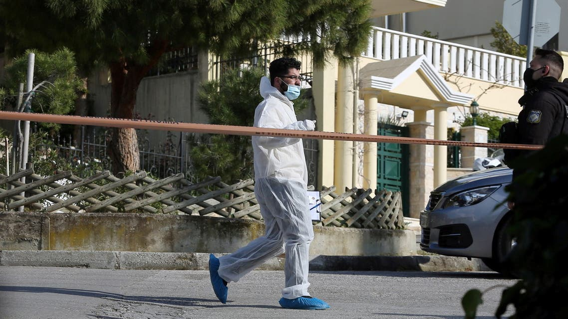 A forensic expert is seen on the road where Greek journalist George Karaivaz was fatally shot in the Alimos suburb of Athens, Greece, April 9, 2021. (Reuters)