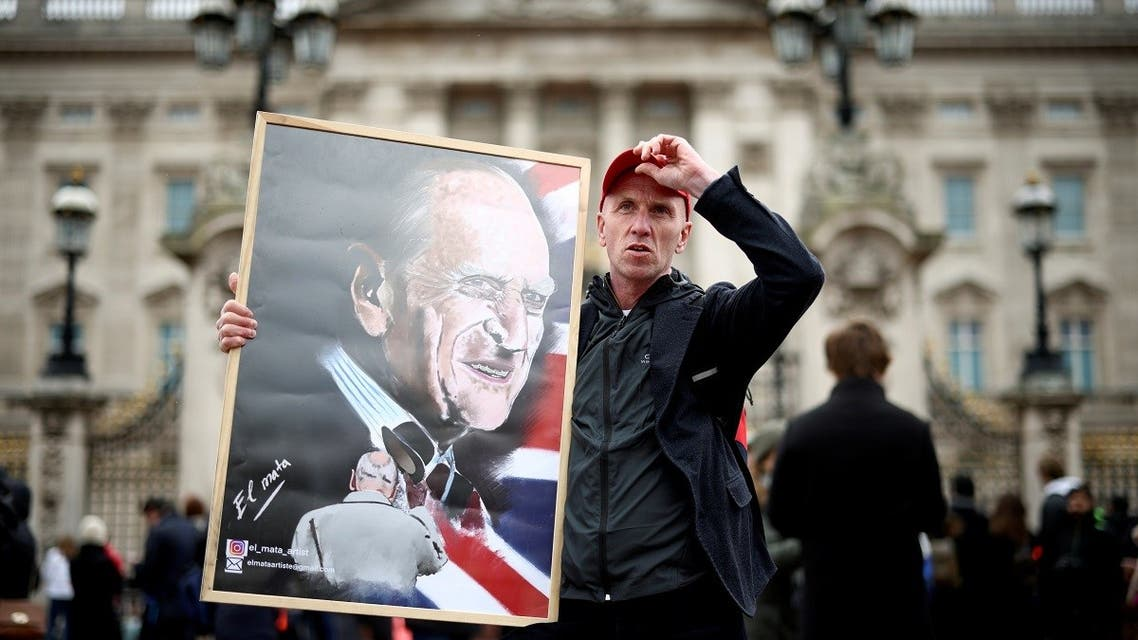 A man holds a poster depicting late Britain's Prince Philip, husband of Queen Elizabeth, who died at the age of 99, outside Buckingham Palace in London, Britain. (Reuters)