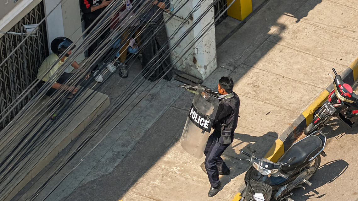 A policeman points his weapon at people in Taunggyi, a city in Shan State, on February 28, 2021, as security forces continue to crackdown on demonstrations by protesters against the military coup.