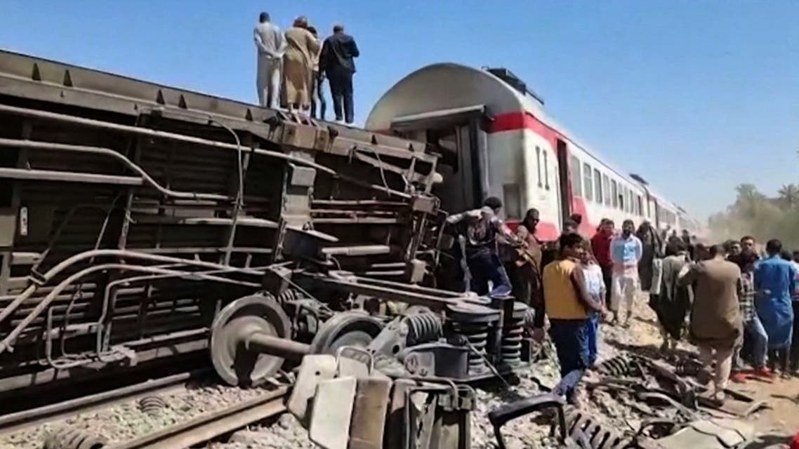 This screengrab provided by AFPTV shows people gathered around the wreckage of two trains that collided in the Sohag province, south of the Egyptian capital Cairo, on March 26, 2021. (AFP)