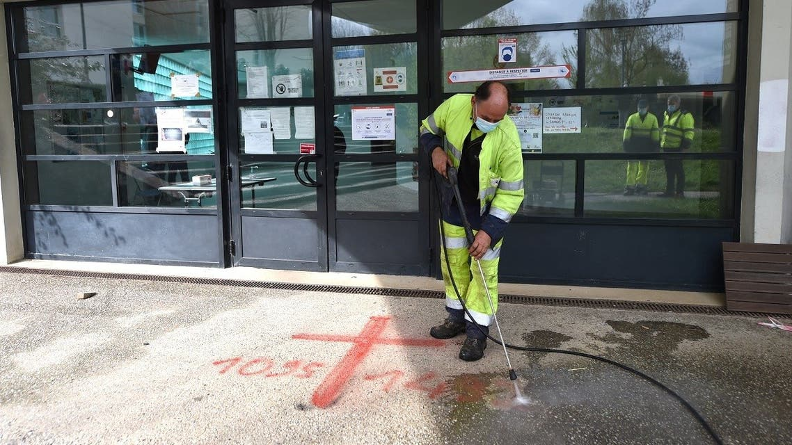 A municipal worker cleans sprayed graffiti outside the Avicenna Islamic Cultural center discovered by early morning Muslim worshippers in Rennes, western France on April 11, 2021. (Jean-Francois Monier/AFP)