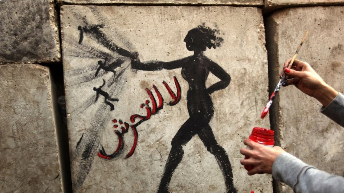 An Egyptian activist draws graffiti depicting a woman and reading in Arabic: No to Sexual Harassement on a wall outside the presidential palace in Cairo on December 14, 2012. (AFP)