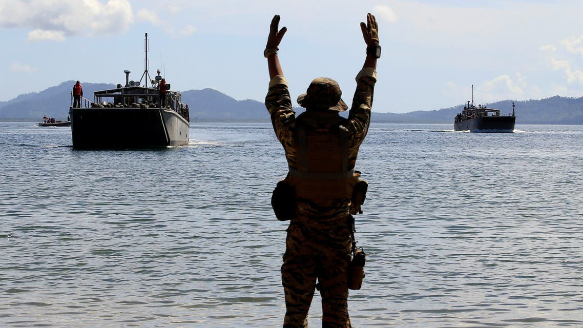 A Filipino soldier displays a hand signal to the landing ships before it docks at Motiong beach, as part of the Humanitarian Assistance and Disaster Response scenario during the Philippines and United States annual Balikatan (Shoulder-to-Shoulder) exercises in Casiguran, Philippines May 15, 2017. (Reuters)