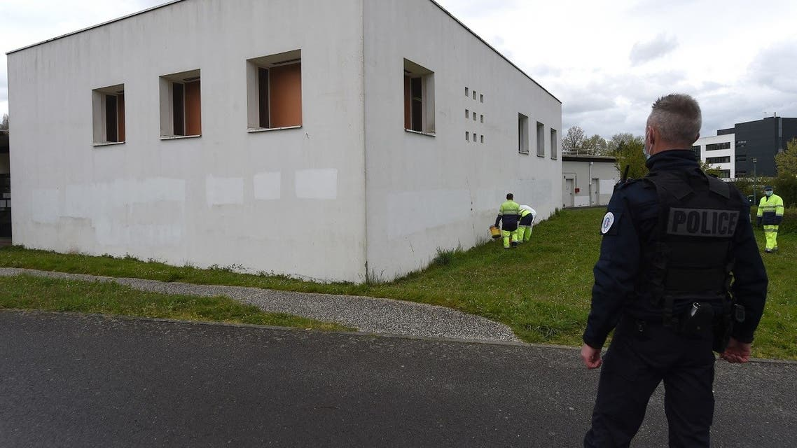 A French police officer watches municipal workers painting the exterior walls of the Avicenna Islamic Cultural center in an attempt to cover-up anti-Muslim graffiti discovered by early morning Muslim worshippers in Rennes, western France on April 11, 2021. (Jean-Francois Monier/AFP)