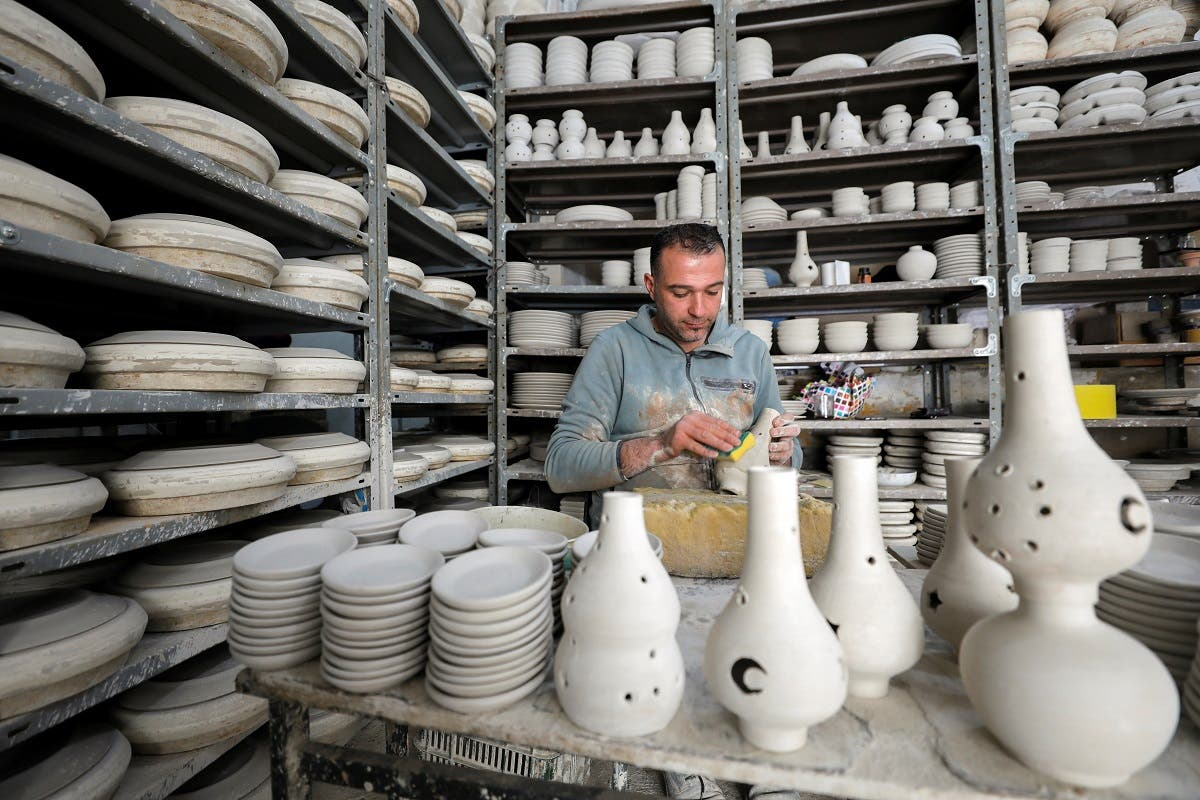A Palestinian man works on ceramic pots for sale ahead of the holy fasting month of Ramadan, in Hebron in the Israeli-occupied West Bank on April 12, 2021. (Reuters)