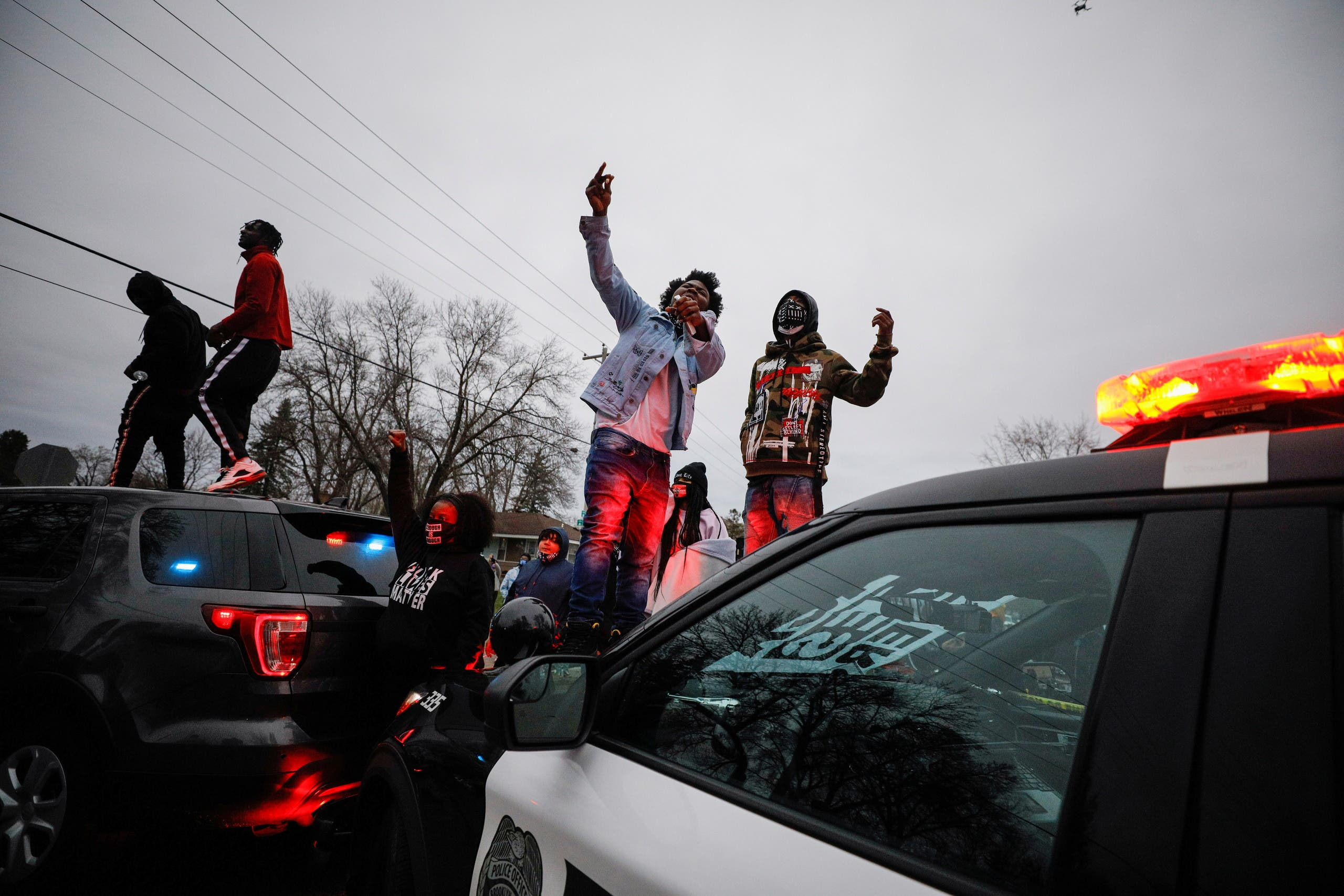 Demonstrators stand on a police vehicle during a protest after police allegedly shot and killed a man, who local media report is identified by the victim's mother as Daunte Wright, in Brooklyn Center, Minnesota, US, April 11, 2021. (Reuters)