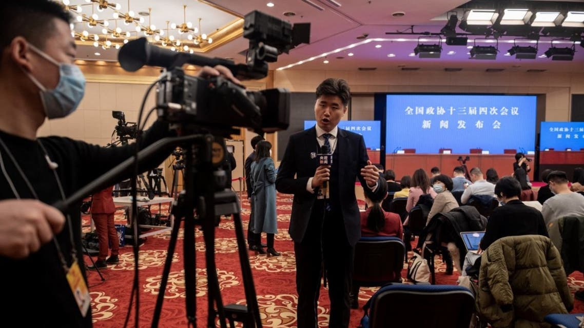 A television journalist works ahead of a press conference at the media centre of the fourth session of the 13th Chinese People's Political Consultative Conference (CPPCC) in Beijing on March 3, 2021. (AFP)
