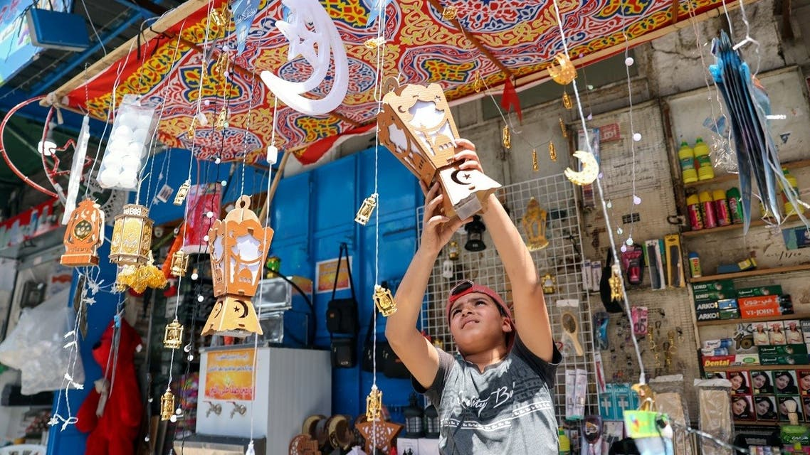 A Palestinian boy hangs a lantern as he sells products at a market, ahead of the holy fasting month of Ramadan, in Gaza City, on April 5, 2021. (Reuters)